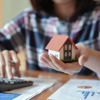 Home salesman holding a model house in hand,other hand uses the calculator.