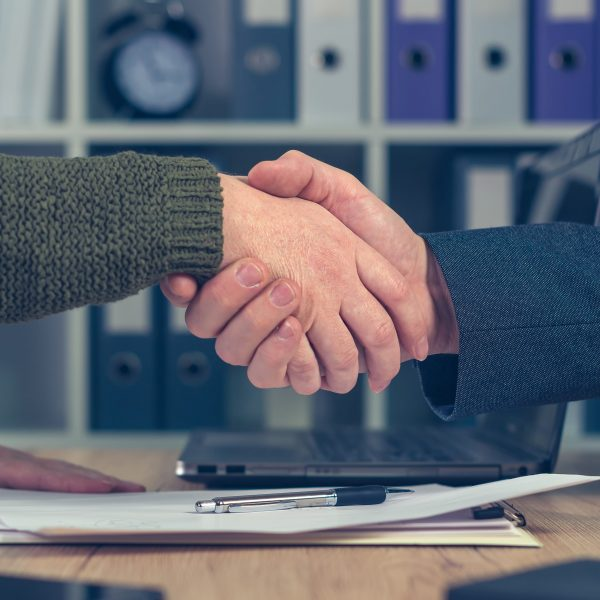 Man and woman shake hands over business agreement. Start up business female entrepreneur making handshake deal with large corporate company for selling small business.